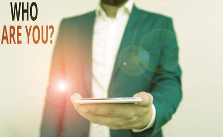 Word writing text Who Are You Question. Business photo showcasing asking about someone identity or demonstratingal information Business concept with man holding mobile phone with touch screen 写真素材