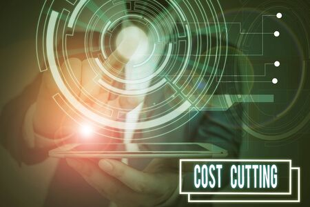 Text sign showing Cost Cutting. Business photo showcasing actions taken to reduce the amount that is spent on a service Male human wear formal work suit presenting presentation using smart device Фото со стока