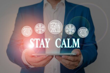 Writing note showing Stay Calm. Business concept for Maintain in a state of motion smoothly even under pressure Male wear formal work suit presenting presentation smart device Stock Photo