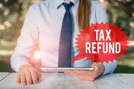 Word writing text Tax Refund. Business photo showcasing applied when money liability is less than the paid ones Female business person sitting by table and holding mobile phone