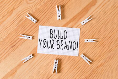 Conceptual hand writing showing Build Your Brand. Concept meaning creates or improves customers knowledge and opinions of product Colored crumpled papers wooden floor background clothespin Фото со стока