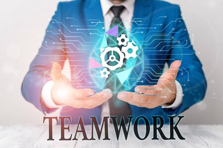 Writing note showing Teamwork. Business concept for Group of showing who work together as one and with the same aim Male human wear formal suit presenting using smart device Stock fotó