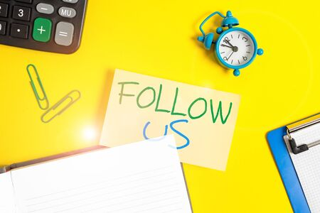 Text sign showing Follow Us. Business photo showcasing Act of demonstrating to invite an individual or group to join his company Empty orange paper with copy space on the yellow table Stockfoto