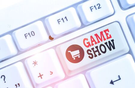 Text sign showing Game Show. Business photo text Program in television or radio with players that win prizes White pc keyboard with empty note paper above white background key copy space
