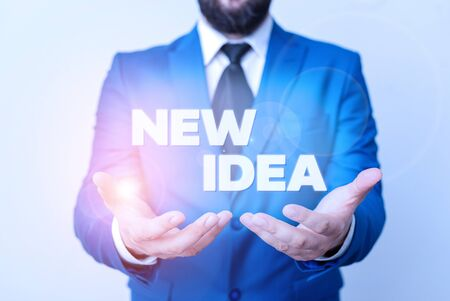 Text sign showing New Idea. Business photo showcasing A thought or conception refer to a product of mental activity Man with opened hands in fron of the table. Mobile phone and notes on the table