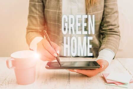 Writing note showing Green Home. Business concept for An area filled with plants and trees where you can relax Business woman sitting with mobile phone and cup of coffee on the table 免版税图像