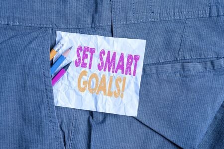 Text sign showing Set Smart Goals. Business photo showcasing list to clarify your ideas focus efforts use time wisely Writing equipment and white note paper inside pocket of man work trousers