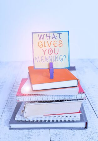 Word writing text What Gives You Meaning Question. Business photo showcasing your purpose or intentions in life pile stacked books notebook pin clothespin colored reminder white wooden Stock Photo