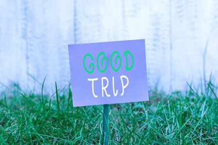 Writing note showing Good Trip. Business concept for A journey or voyage,run by boat,train,bus,or any kind of vehicle Plain paper attached to stick and placed in the grassy land Stock fotó