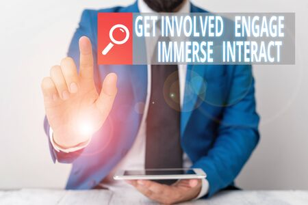 Writing note showing Get Involved Engage Immerse Interact. Business concept for Join Connect Participate in the project Businessman with pointing finger in front of him