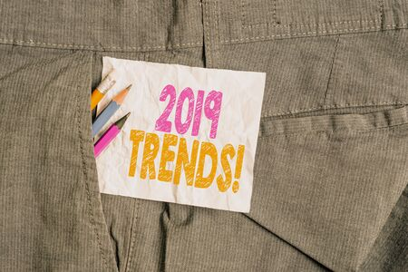 Text sign showing 2019 Trends. Business photo showcasing general direction in which something is developing or changing Writing equipment and white note paper inside pocket of man work trousers Stock fotó