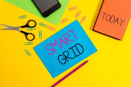 Handwriting text writing Smart Grid. Conceptual photo includes of operational and energy measures including meters Paper sheets pencil clips smartphone scissors notebook colored background