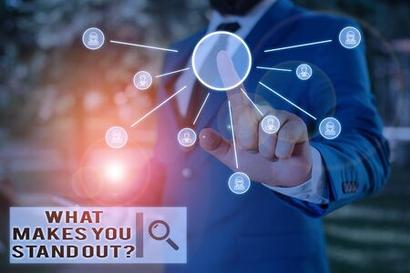 Text sign showing What Makes You Stand Out Question. Business photo text asking someone about his qualities Male human wear formal work suit presenting presentation using smart device