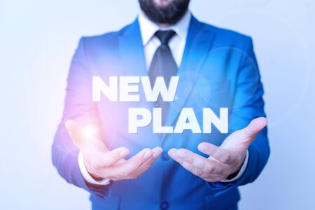 Text sign showing New Plan. Business photo showcasing Start of a detailed proposal of doing or achieving something Man with opened hands in fron of the table. Mobile phone and notes on the table