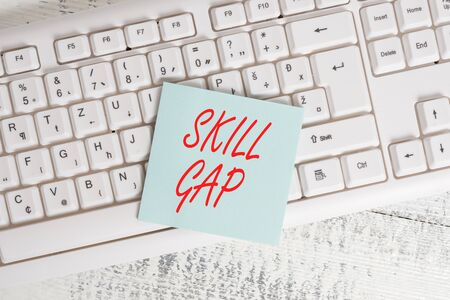 Conceptual hand writing showing Skill Gap. Concept meaning Refering to a demonstrating s is weakness or limitation of knowlege Keyboard office supplies rectangle shape paper reminder wood