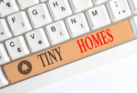 Word writing text Tiny Homes. Business photo showcasing houses contain one room only or two and small entrance Cheap White pc keyboard with empty note paper above white background key copy space