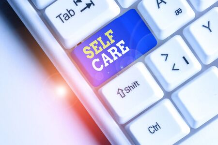 Conceptual hand writing showing Self Care. Concept meaning Give comfort to your own body without professional consultant White pc keyboard with note paper above the white background