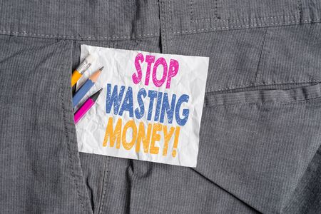 Text sign showing Stop Wasting Money. Business photo showcasing advicing demonstrating or group to start saving and use it wisely Writing equipment and white note paper inside pocket of man work trousers