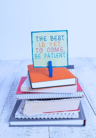 Word writing text The Best Is Yet To Come Be Patient. Business photo showcasing dont lose hope light come after darkness pile stacked books notebook pin clothespin colored reminder white wooden