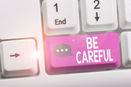 Writing note showing Be Careful. Business concept for making sure of avoiding potential danger mishap or harm White pc keyboard with note paper above the white background Stock Photo