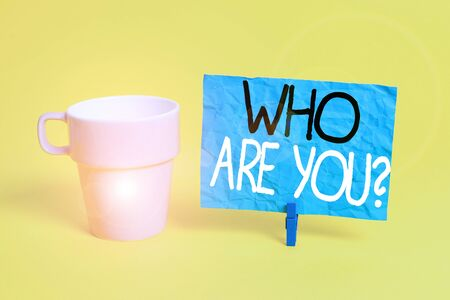 Handwriting text Who Are You Question. Conceptual photo asking about someone identity or demonstratingal information Cup empty paper blue clothespin rectangle shaped reminder yellow office