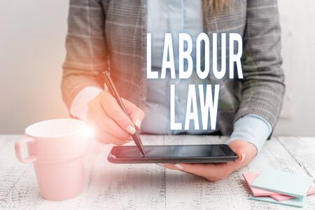 Writing note showing Labour Law. Business concept for Rules implemented by the state between employers and employee Business woman sitting with mobile phone and cup of coffee on the table
