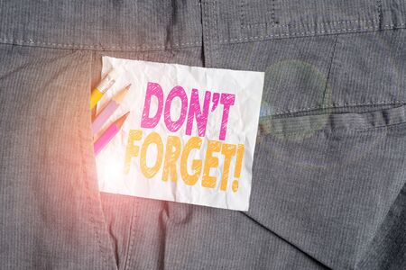 Text sign showing Don T Forget. Business photo showcasing used to remind someone about important fact or detail Writing equipment and white note paper inside pocket of man work trousers Reklamní fotografie