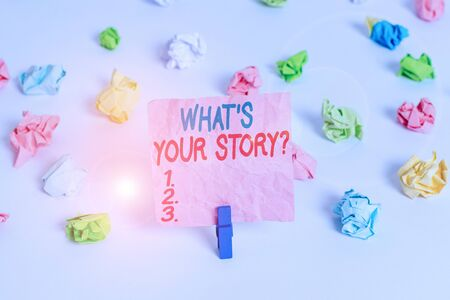 Conceptual hand writing showing What S Your Story Question. Concept meaning asking demonstrating about his past life actions career or events Colored crumpled paper empty reminder white floor clothespin