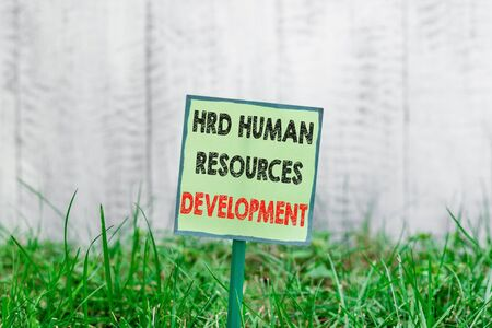 Conceptual hand writing showing Hrd Huanalysis Resources Development. Concept meaning helping employees develop demonstratingal skills Plain paper attached to stick and placed in the grassy land