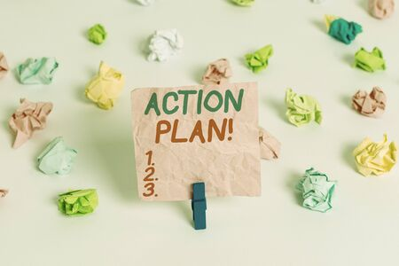 Conceptual hand writing showing Action Plan. Concept meaning proposed strategy or course of actions for certain time Colored crumpled paper empty reminder white floor clothespin Фото со стока