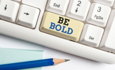 Writing note showing Be Bold. Business concept for Go for it Fix it yourself instead of just talking Tough Hard White pc keyboard with note paper above the white background