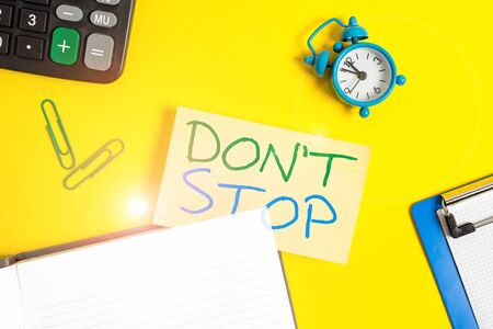 Text sign showing Don't Stop. Business photo showcasing Continue what had been doing without rendering a delay Empty orange paper with copy space on the yellow table