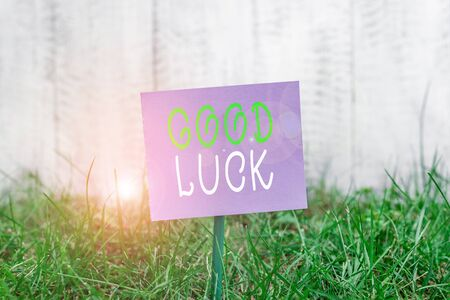Writing note showing Good Luck. Business concept for A positive fortune or a happy outcome that a demonstrating can have Plain paper attached to stick and placed in the grassy land
