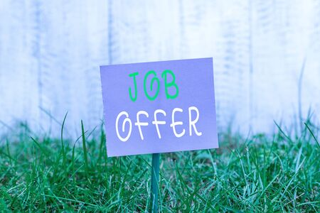 Writing note showing Job Offer. Business concept for A peron or company that gives opurtunity for one s is employment Plain paper attached to stick and placed in the grassy land