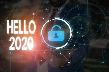 Conceptual hand writing showing Hello 2020. Concept meaning expression or gesture of greeting answering the telephone Male wear formal work suit presenting presentation smart device Stockfoto