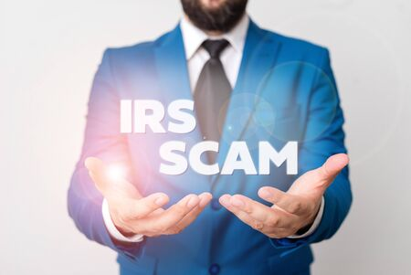 Text sign showing Irs Scam. Business photo showcasing targeted taxpayers by pretending to be Internal Revenue Service Man with opened hands in fron of the table. Mobile phone and notes on the table Stock fotó