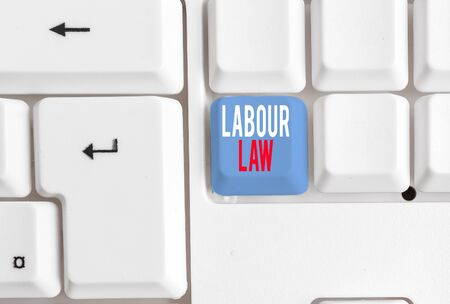 Handwriting text writing Labour Law. Conceptual photo Rules implemented by the state between employers and employee White pc keyboard with empty note paper above white background key copy space