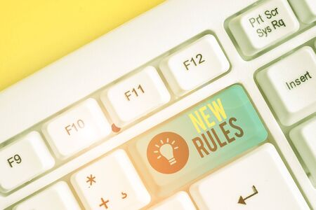 Conceptual hand writing showing New Rules. Concept meaning A state of changing an iplemented policy for better upgrade White pc keyboard with note paper above the white background