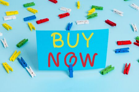 Handwriting text Buy Now. Conceptual photo asking someone to purchase your product Provide good Discount Colored clothespin papers empty reminder blue floor background office pin Foto de archivo - 131386216