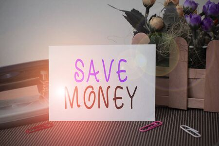 Text sign showing Save Money. Business photo text store some of your cash every month to use them sometime later Flowers and writing equipments plus plain sheet above textured backdrop