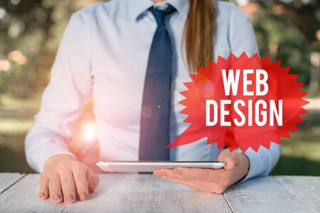 Word writing text Web Design. Business photo showcasing who is responsible of production and maintenance of websites Female business person sitting by table and holding mobile phone Banco de Imagens