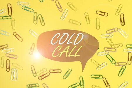 Handwriting text Cold Call. Conceptual photo Unsolicited call made by someone trying to sell goods or services Flat lay above empty paper with copy space and colored paper clips