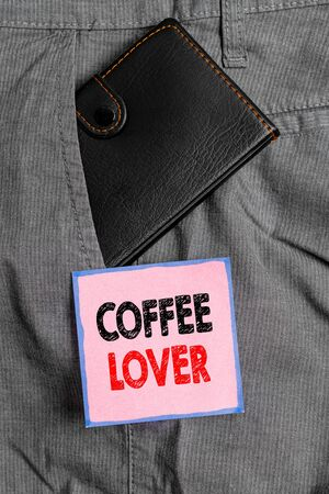 Handwriting text writing Coffee Lover. Conceptual photo a demonstrating who loves or has a fondness of drinking coffee Small little wallet inside man trousers front pocket near notation paper 版權商用圖片