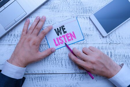 Writing note showing We Listen. Business concept for Group of showing that is willing to hear anything you want to say