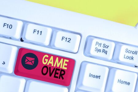 Text sign showing Game Over. Business photo text A situation in a particular sport that reach his finals or ending White pc keyboard with empty note paper above white background key copy space