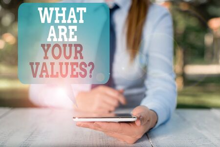Writing note showing What Are Your Values Question. Business concept for asking someone about his good qualities Female business person sitting by table and holding mobile phone