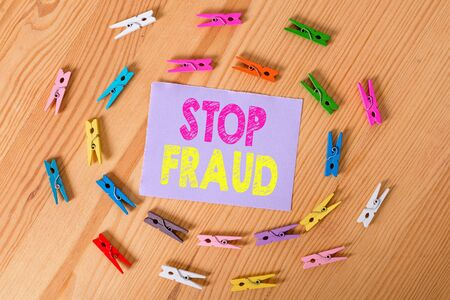Handwriting text Stop Fraud. Conceptual photo campaign advices showing to watch out thier money transactions Colored clothespin papers empty reminder wooden floor background office