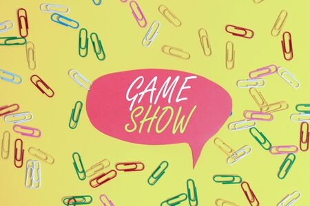 Handwriting text Game Show. Conceptual photo Program in television or radio with players that win prizes Flat lay above empty paper with copy space and colored paper clips Stok Fotoğraf