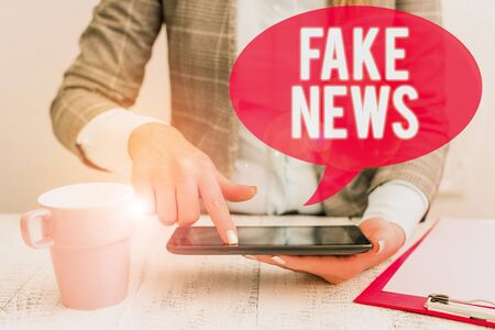 Text sign showing Fake News. Business photo showcasing Giving information to showing that is not true by the media Business woman sitting with mobile phone and cup of coffee on the table