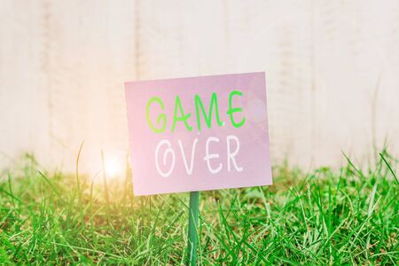 Writing note showing Game Over. Business concept for A situation in a particular sport that reach his finals or ending Plain paper attached to stick and placed in the grassy land
